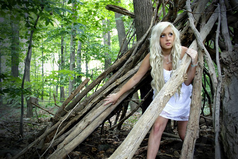 woman under piled trees wearing a white dress photo
