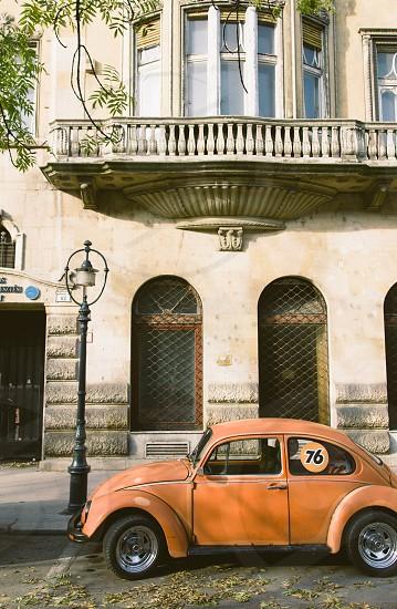 orange Volkswagen beetle parked near the light post photo