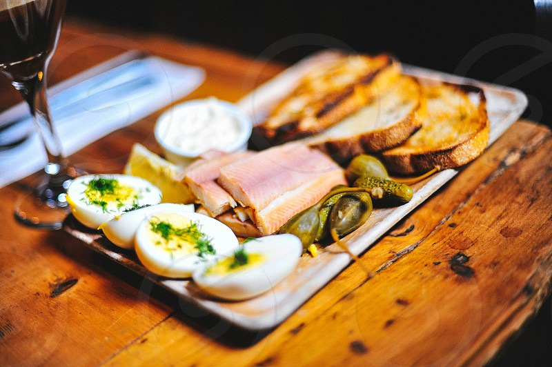 deviled eggs brown eggs green pickles and pink meat on rectangle tray on brown wooden table photo