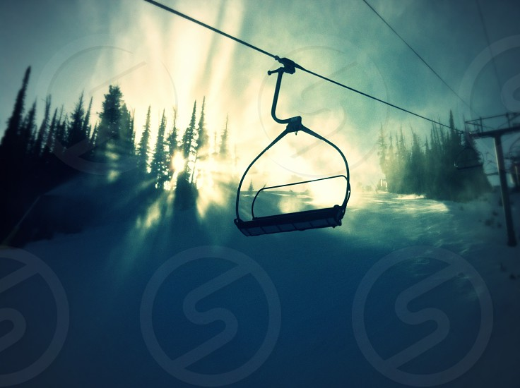 Vacant chairlift passing over sun-drenched ski slope. photo