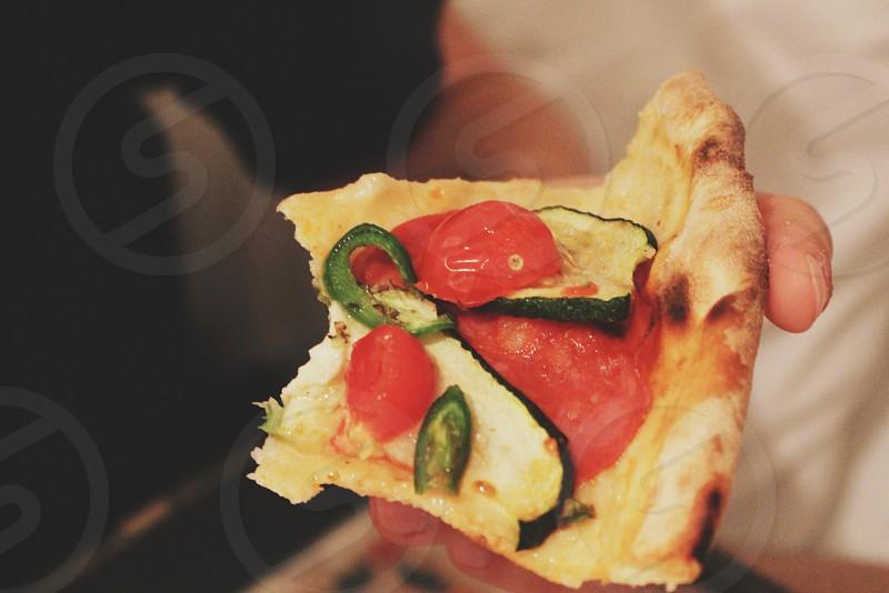 person holding a slice of pizza with fresh tomatoes and zucchini photo