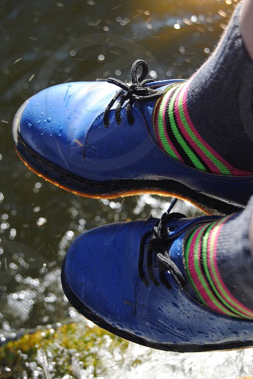 person wearing blue leather shoes wearing gray pink green stripe socks photo