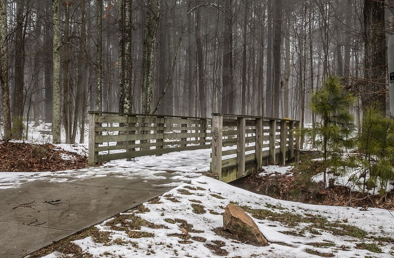 grey wooden bridge coated with snow photo