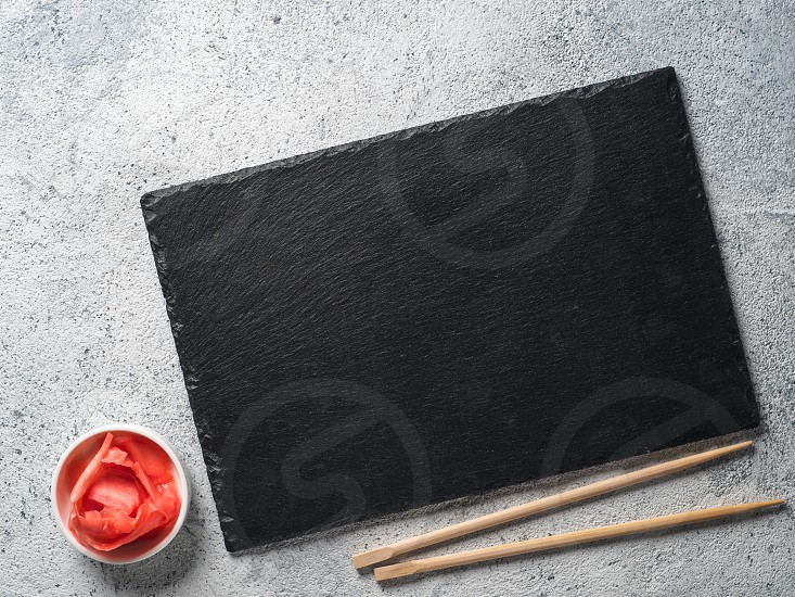 Empty slate plate on gray cement background with chopsticks and pickled ginger. Copy space. Top view or flat-lay. Concept for restaurant and delivery sushi and rolls photo