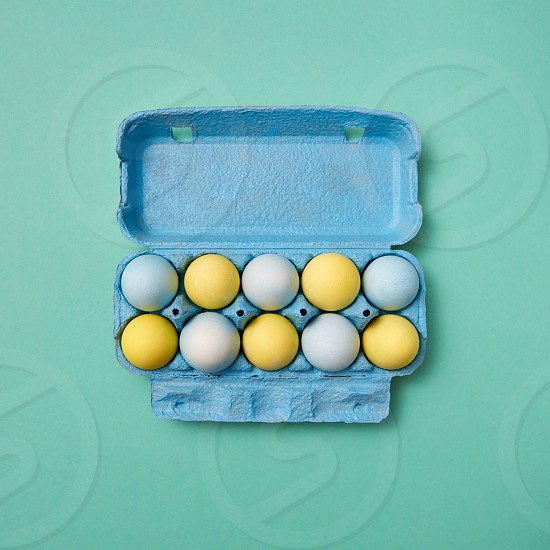 Multicolored painted in yellow blue eggs in a blue cardboard box on a green background with copy space. Easter composition. Flat lay photo