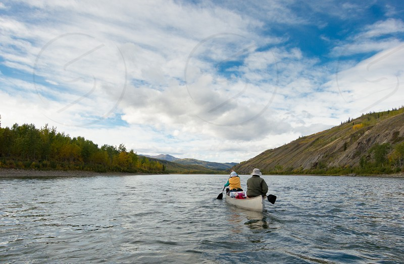 A couple of canoeists on wilderness adventure trip paddling wide Pelly River central Yukon Territory Canada photo