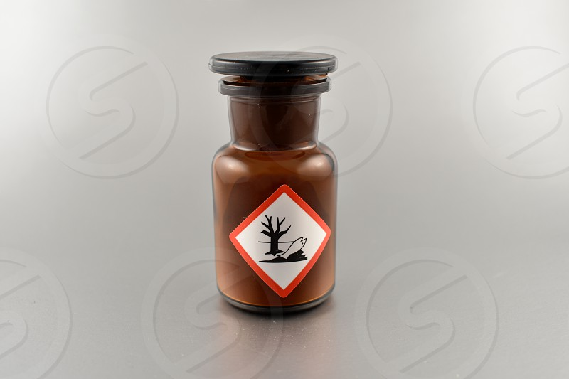 Vial with warning pictogram. Laboratory accessories. Vial on a silver background. Brown glass containers. Brown chemical glass photo