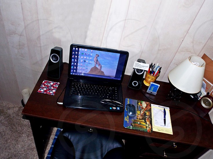 black laptop turned on between speakers on brown wooden table photo