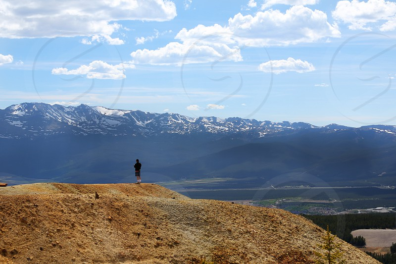 Man standing on a mountain overlooking more mountains in the distance in Colorado photo