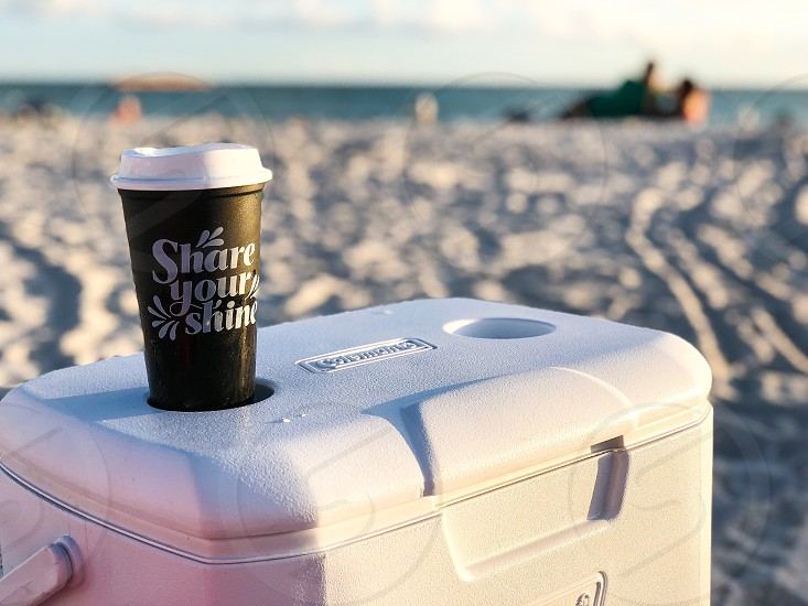Coffee cups around the world beach sand sunset summertime golden hour people ice chest coolercoffee cup photo