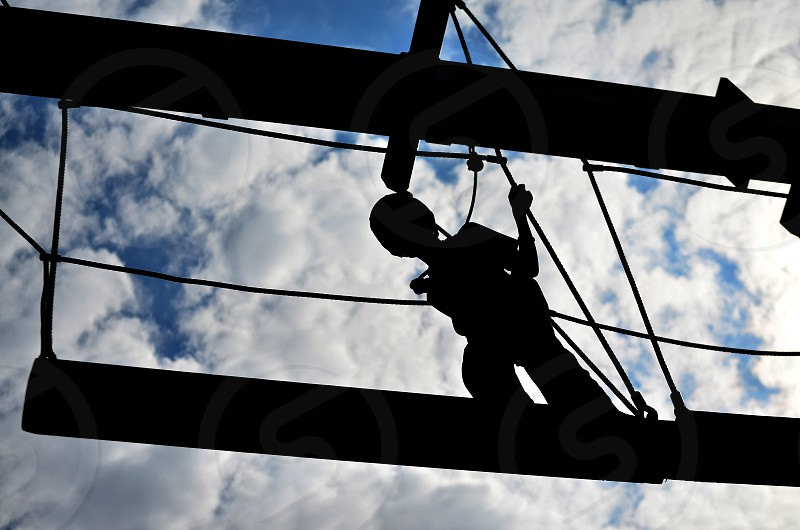 Silhouette of a person completing a high-ropes course with cloudy blue sky. photo