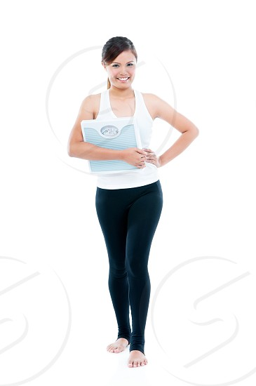 Full-length portrait of a happy fitness woman holding weight scale over white background photo