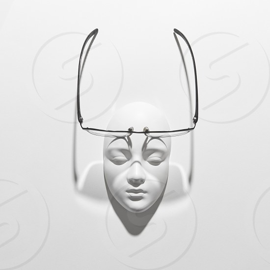 Plaster face mask with elegant glasses above it on a white background with soft long shadows copy space. Flat lay. photo
