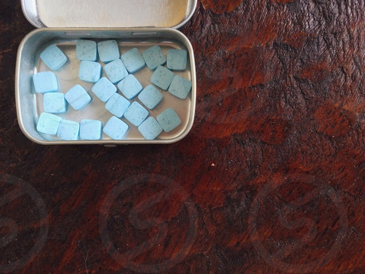 blue square shaped tablets inside the stainless steel container photo