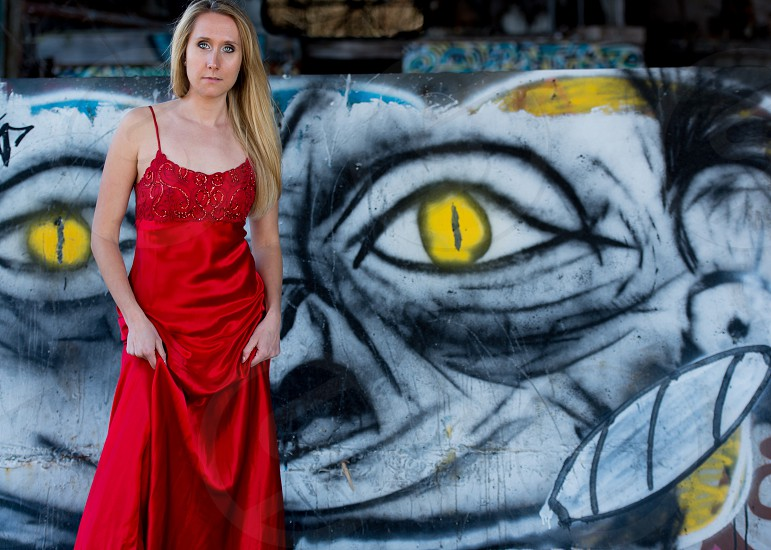 Beautiful young woman in red formal dress. Warehouse with graffiti and gritty environment.  photo