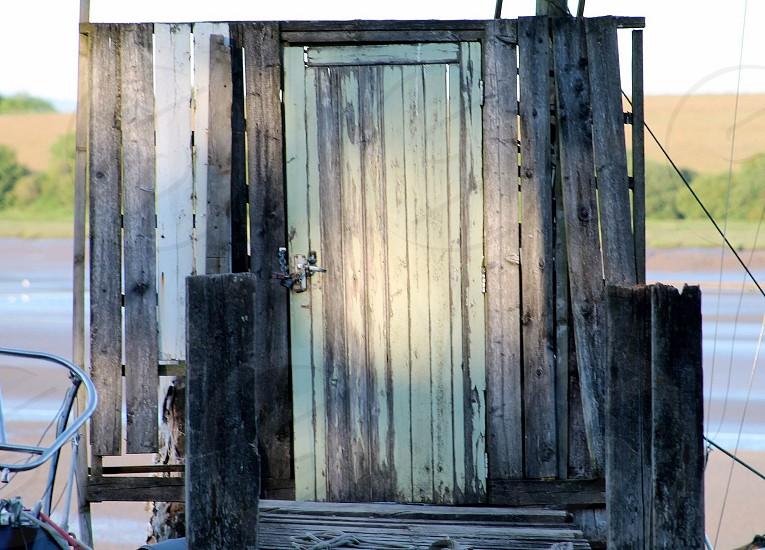Doorway to where?sunseasandboatdoorwoodcolourfulgreensunlightlockchainhandlestepboardwalk photo