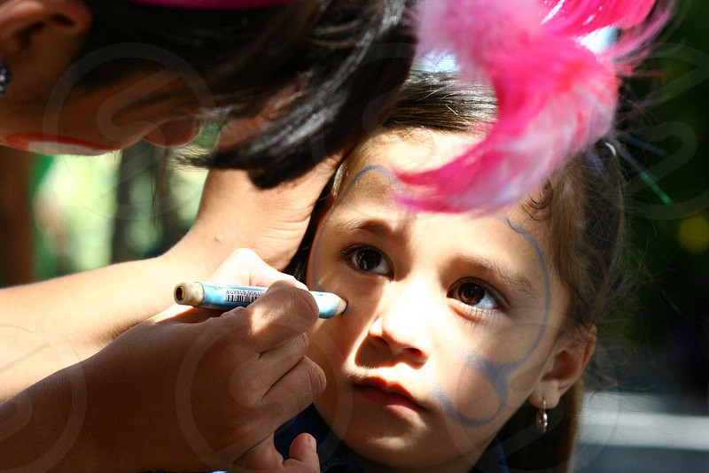 Girl being painted on her face at a family party photo