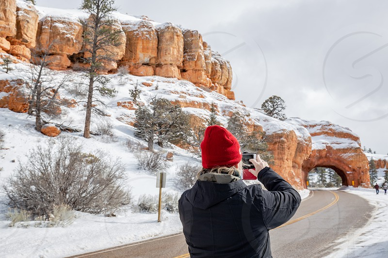 Woman taking a picture of road through arch in Bryce Canyon photo
