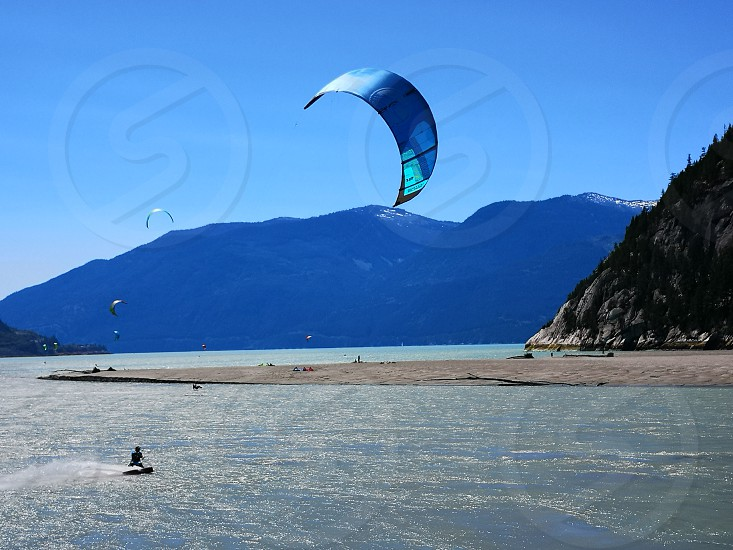 enjoying the nice summer weather by spending the afternoon kite surfing photo