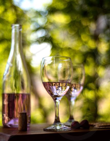 Rosé wine outside wood table green trees light crackers berries cork glasses bottle. photo