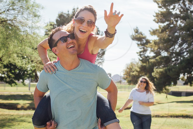 woman running behind woman on man's back photo