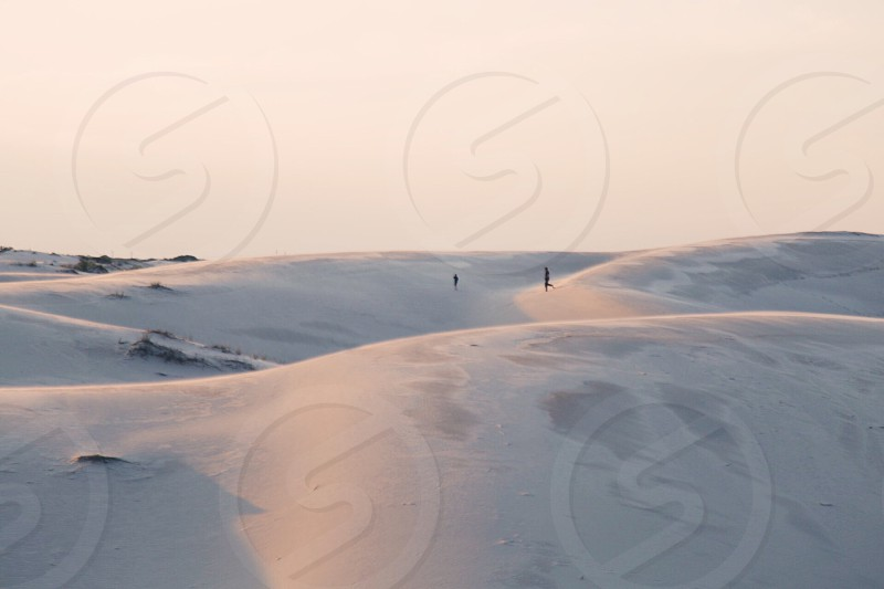 2 people in white sand dunes during d aytime photo