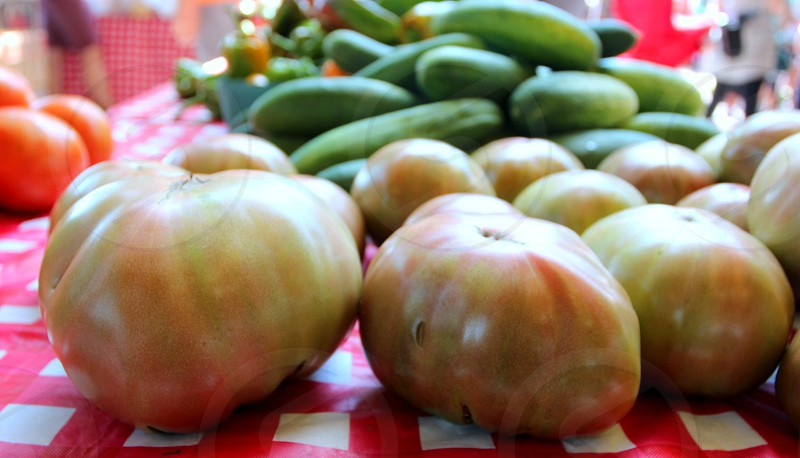 Greenish pink tomatoes and cucumbers at farmers market photo