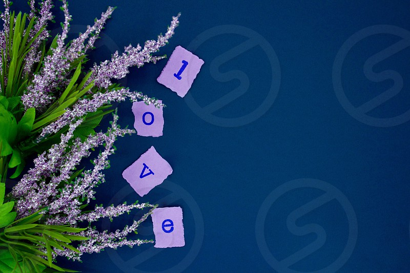"""Lavender flowers and torn squares of lavender paper with the letters spelling """"l-o-v-e"""" stamped in dark blue ink on a dark blue background photo"""