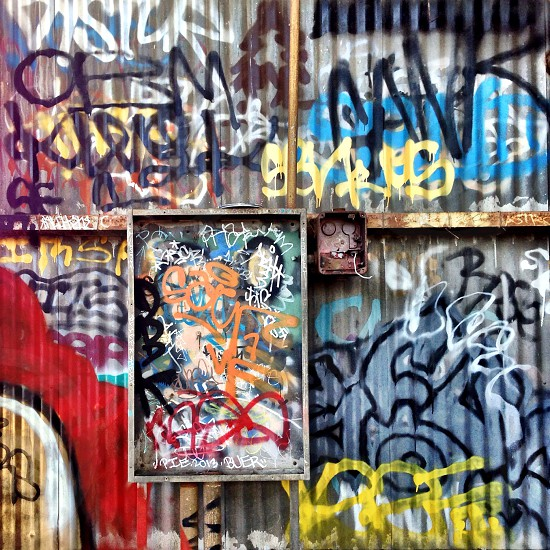 black yellow white and red graffiti text on ribbed grey metal wall panels photo