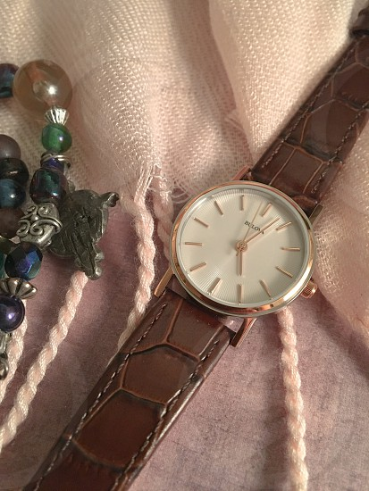 close up photo of brown alligator skin leather strap gold round case white bulova watch beside charm bracelet on pink twisted fringed cloth photo
