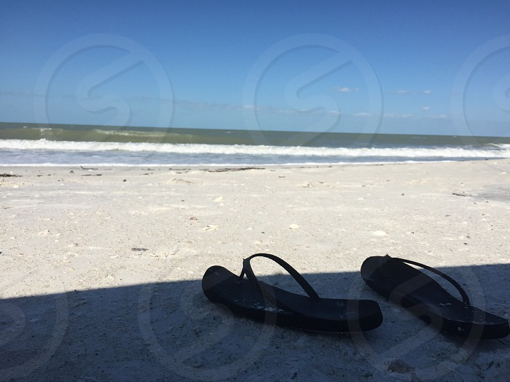 pair of black thong sandals on a gray sand pavement near on body of water photo