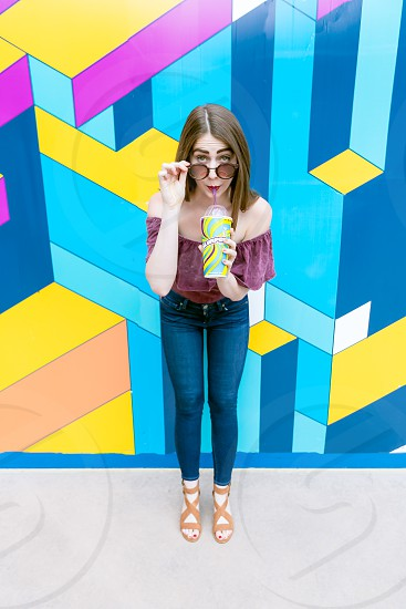 A fun hip girl enjoying a Slurpee in an urban setting.  photo