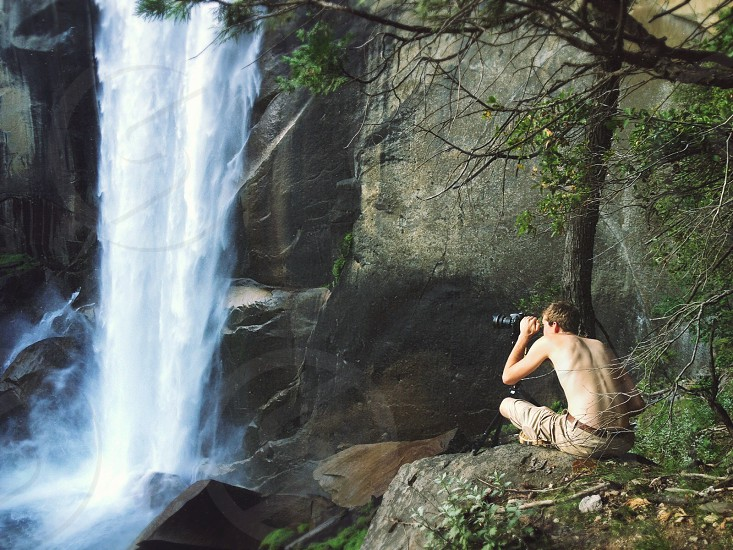 topless man sitting on rock beside tall tree taking photo of waterfalls photo