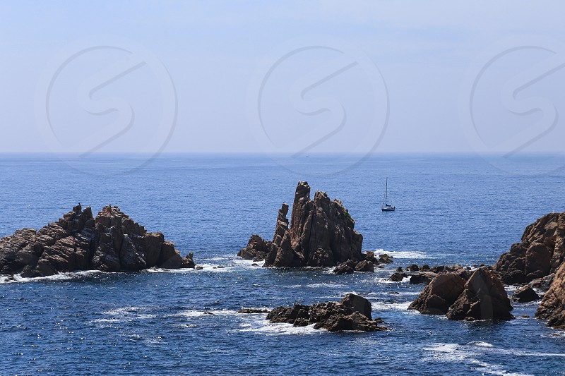 Top view on the rock and a ship in the deep blue sea on a sunny summer day photo