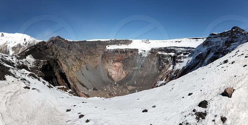 Panorama volcano landscape of Kamchatka Peninsula: large summit crater of active Tolbachik Volcano with steep sides and glaciers. Russian Far East Kamchatka Region Klyuchevskaya Group of Volcanoes. photo