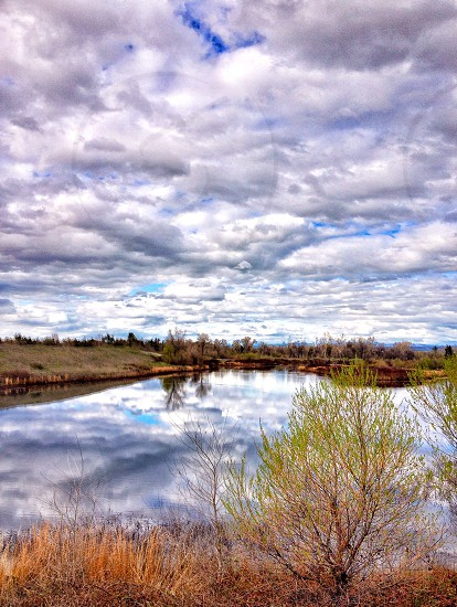 view of a small lake with cloudy skies photo