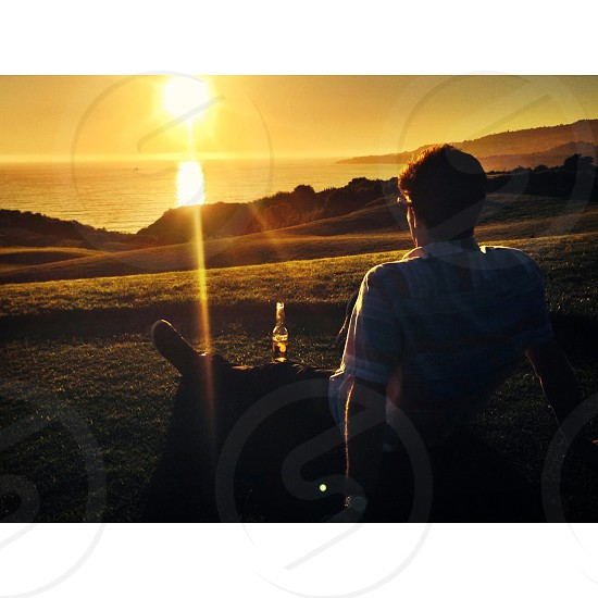 man sitting on the glass covered ground with beer watching the sunset photo