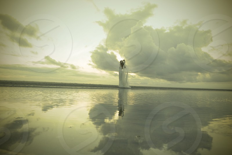 person standing near body of water with clouds reflecting on water photo
