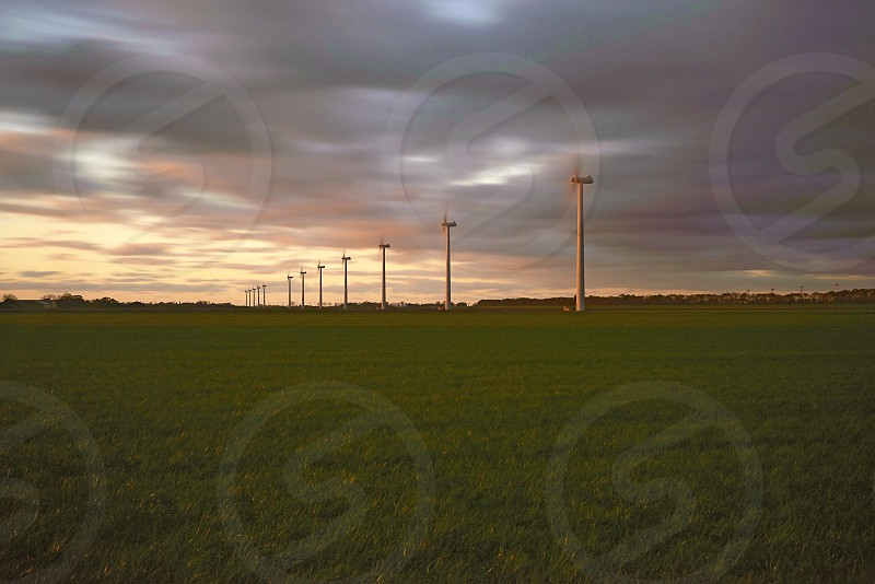 Amazing creative image of a wind farm featuring huge wind turbines in a flat landscape shot in a long exposure to create the movement of the wind photo