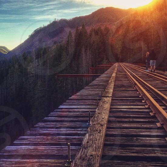 wood train track bridge with people walking on it photo