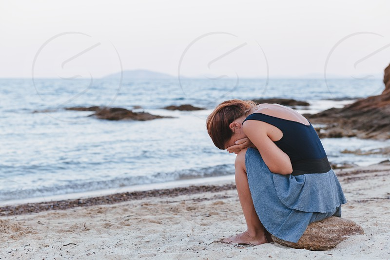 Woman alone and depressed sitting at the beach photo