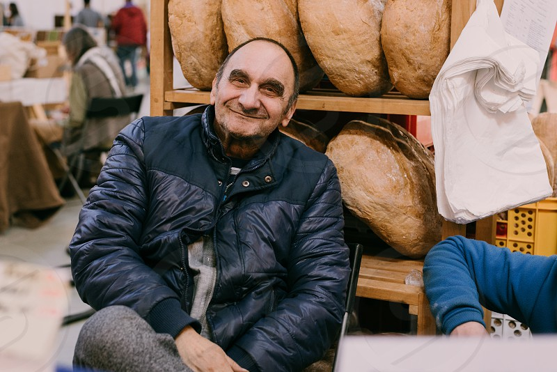 Older man smiling to the camera while selling bread at the local market. photo