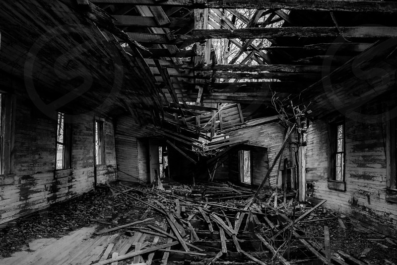 a grayscale photo of a broken wooden house captured during daylight photo