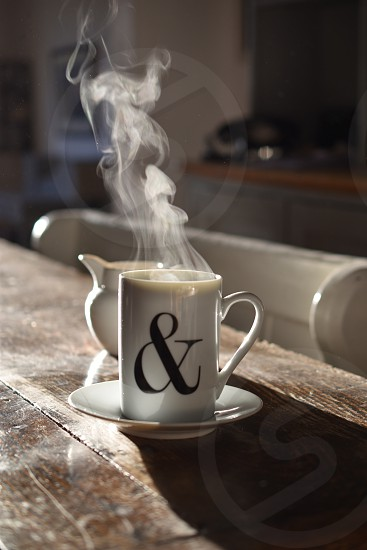Steaming hot drink on wooden kitchen table. photo