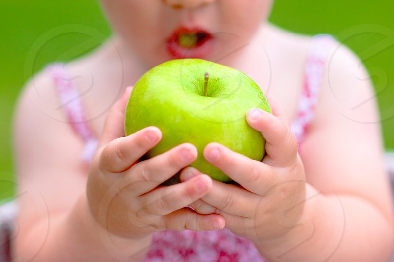 girl in pink dress holding green apple with both hands photo