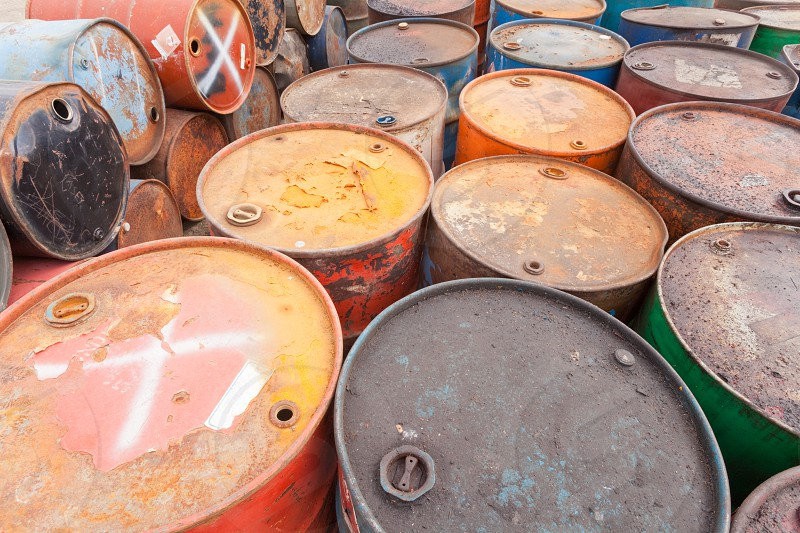 Rows of dirty rusty barrels with toxic industrial waste awaiting proper handling and disposal photo