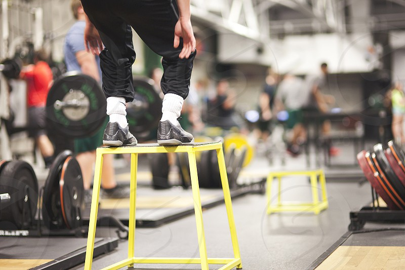 people standing on yellow stool inside gym photo
