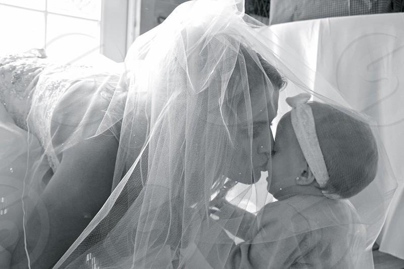 woman wearing wedding dress kissing daughter photo