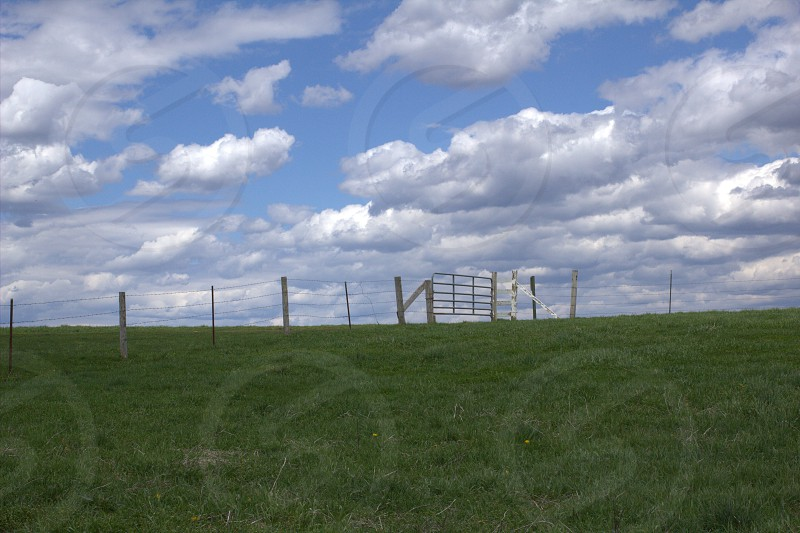 Landscape field clouds fence  gathering storm photo