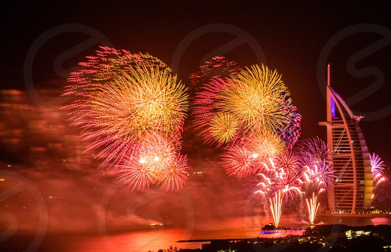 yellow pink orange purple fireworks in  black night sky above lake and by oblong silver metal and glass building photo